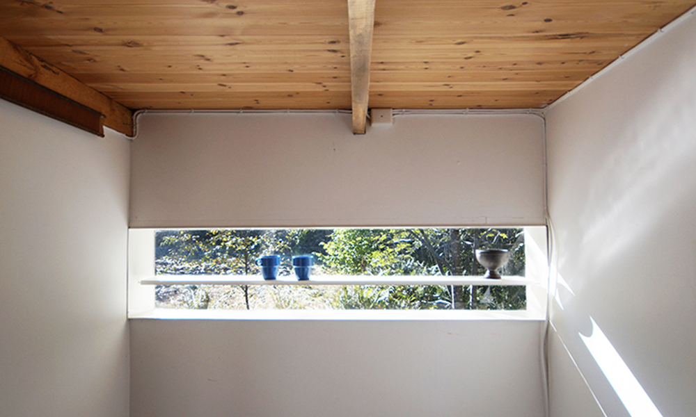 View of Plexiglas window in the hallway with shelf mounted on the window making it look like it is hovering