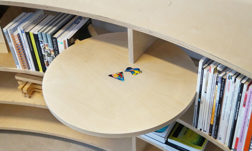 A small library is placed at the back part of the cabinet. The small library table has an acrylic paint logo poured into the recessed wood.